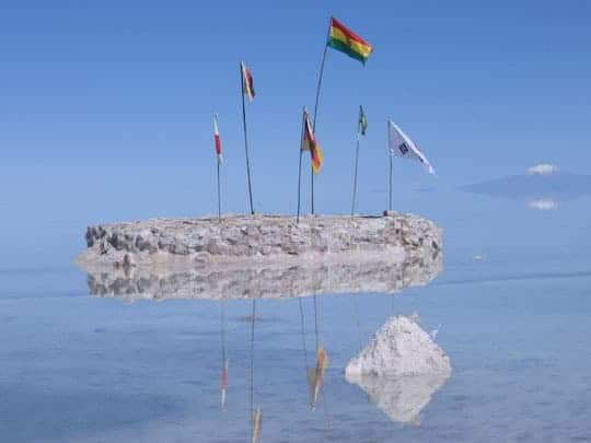 Flags Come Out Of A Small Rock Sticking Out Of The Water