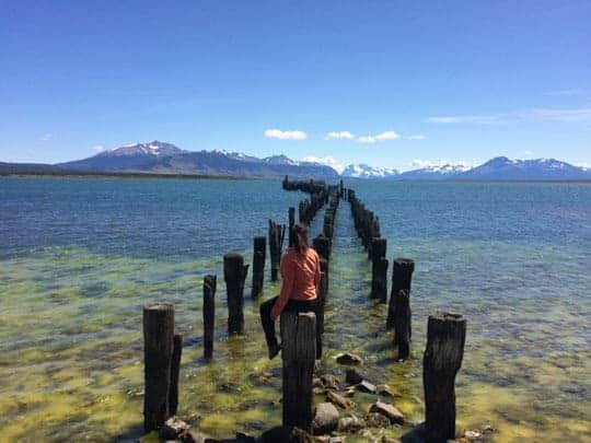 A Girl Sits on a Beam Looking Out to the Water at the Harbour in Puerto Natales, Chile