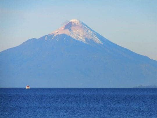 The Volcano Villarrica Towers Over Blue Water