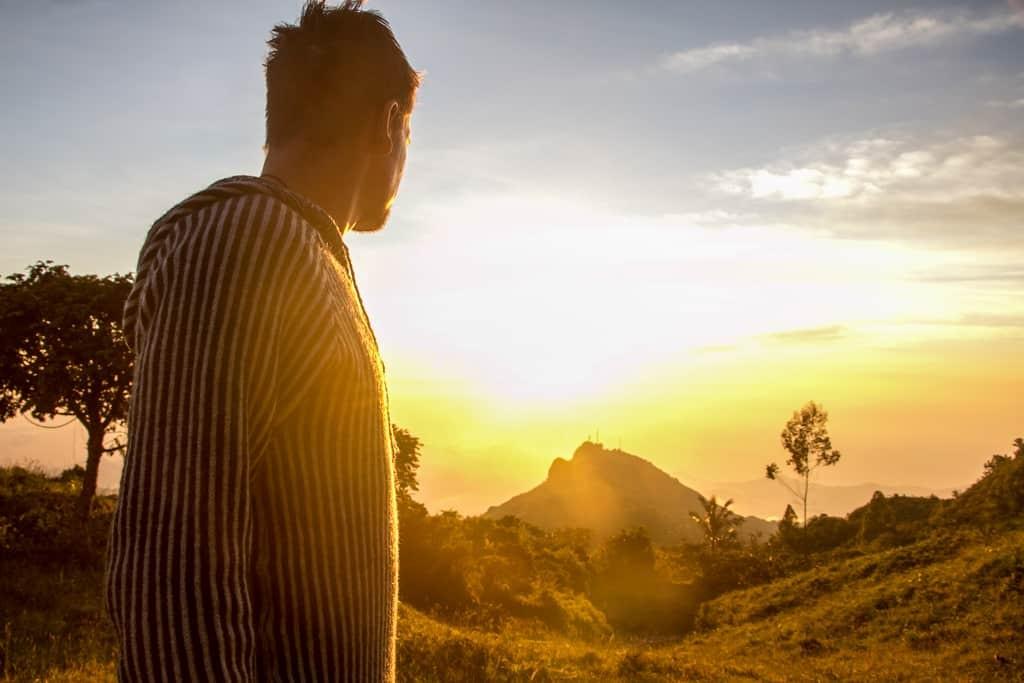 Man overlooks sunset on mountain.