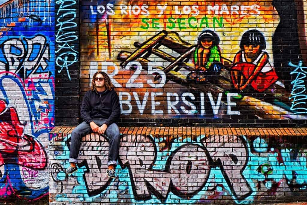 A man sits on a ledge of a heavily graffitied wall in Bogotá