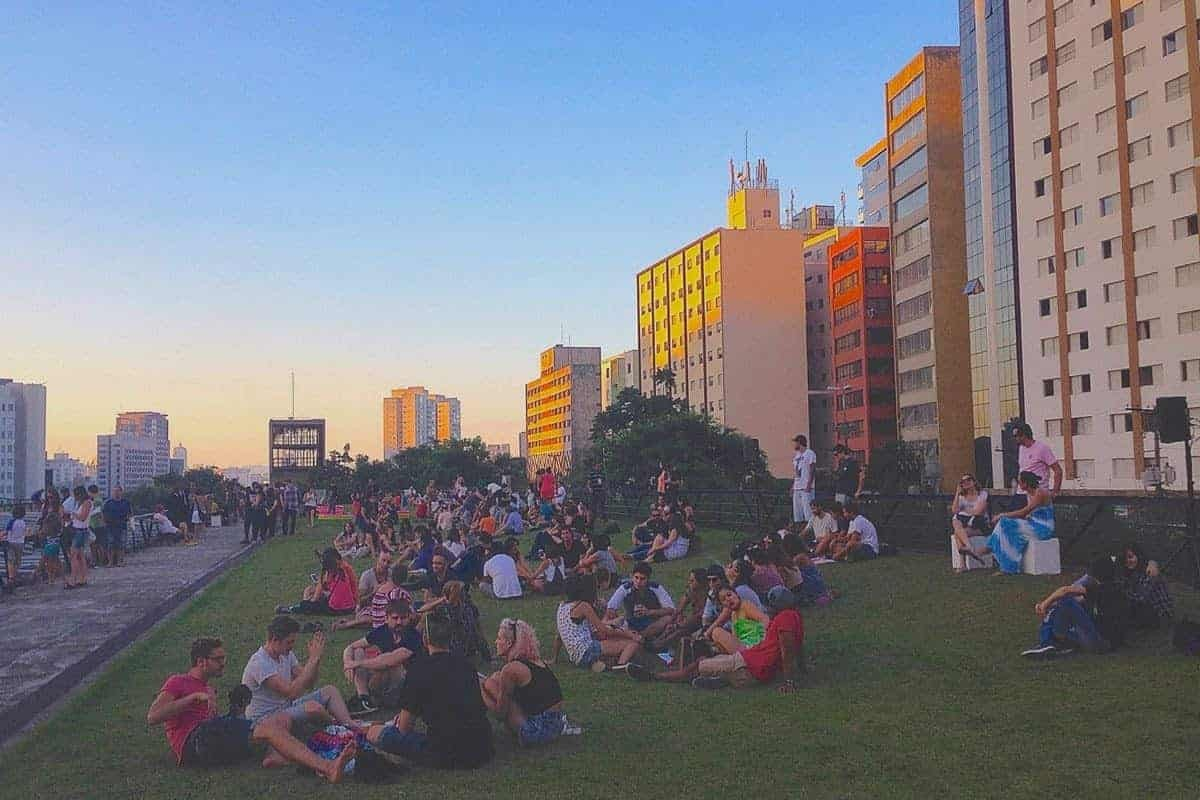 Groups of people sit on the grass by some skyscrapers in Sao Paulo