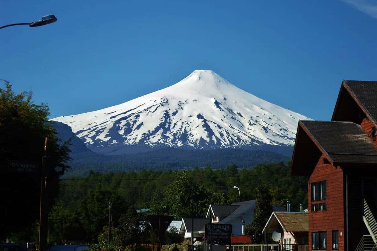 A snowy mountain seen over wooden houses and a forest, Pucón, Chile