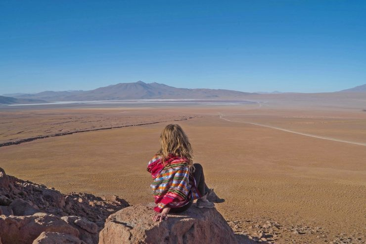 A Girl Sits on a Rock in The Desert, The Main Picture For an Article About Backpacking in South America Routes