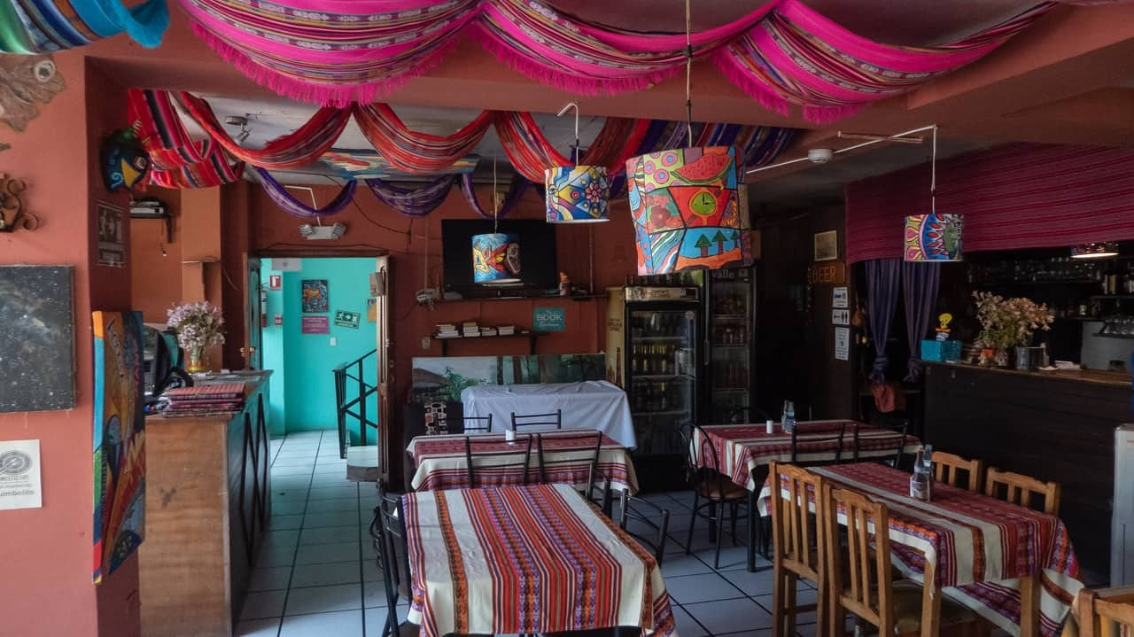 Vibrant hues in the restaurant emphasize the lively atmosphere in Erupcion Art Hotel and Hostel, Ecuador