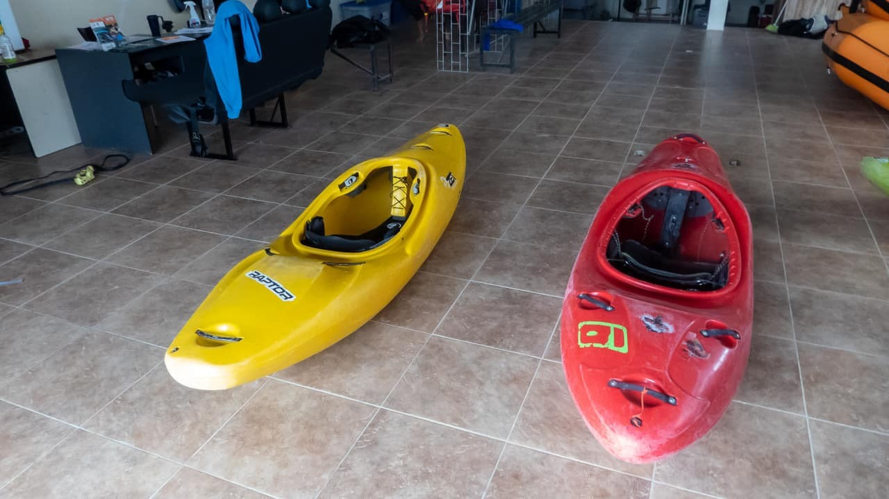 A yellow and a red kayak on the floor, before setting off whitewater kayaking with Kayak Ecuador