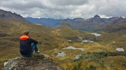 A backpacker looking on the extensive mountain range of Cajas National Park Ecuador