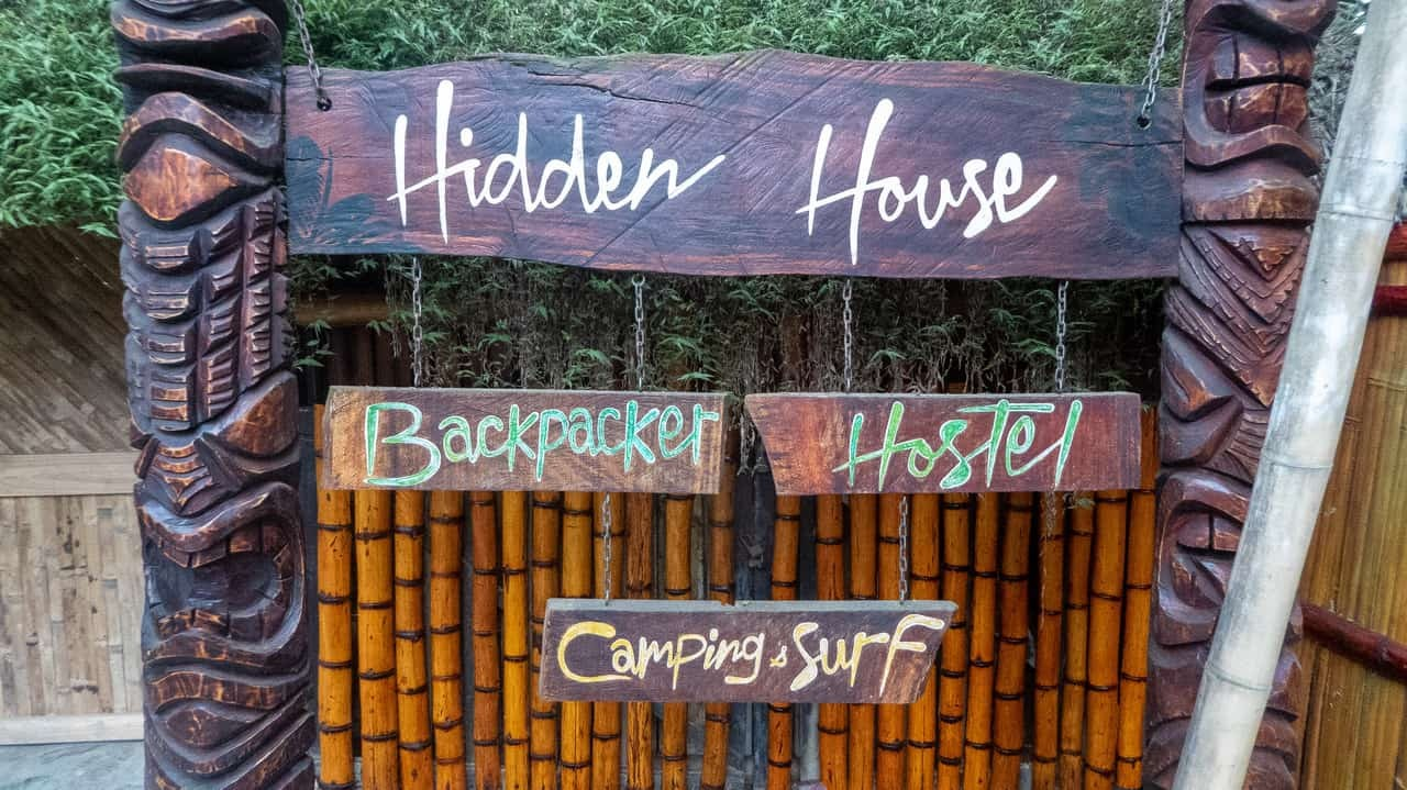 Standing mightily, the artistically carved wooden posts hold the signboard of Hidden House Montañita Ecuador.