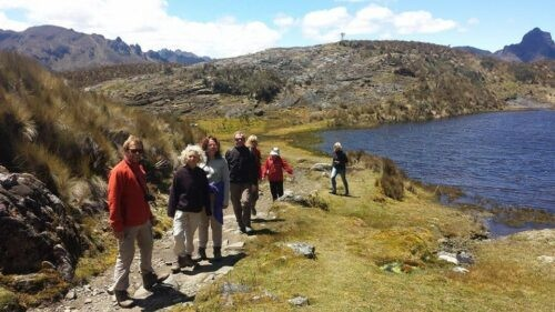 Backpackers trekking by the river in Cajas National Park Ecuador