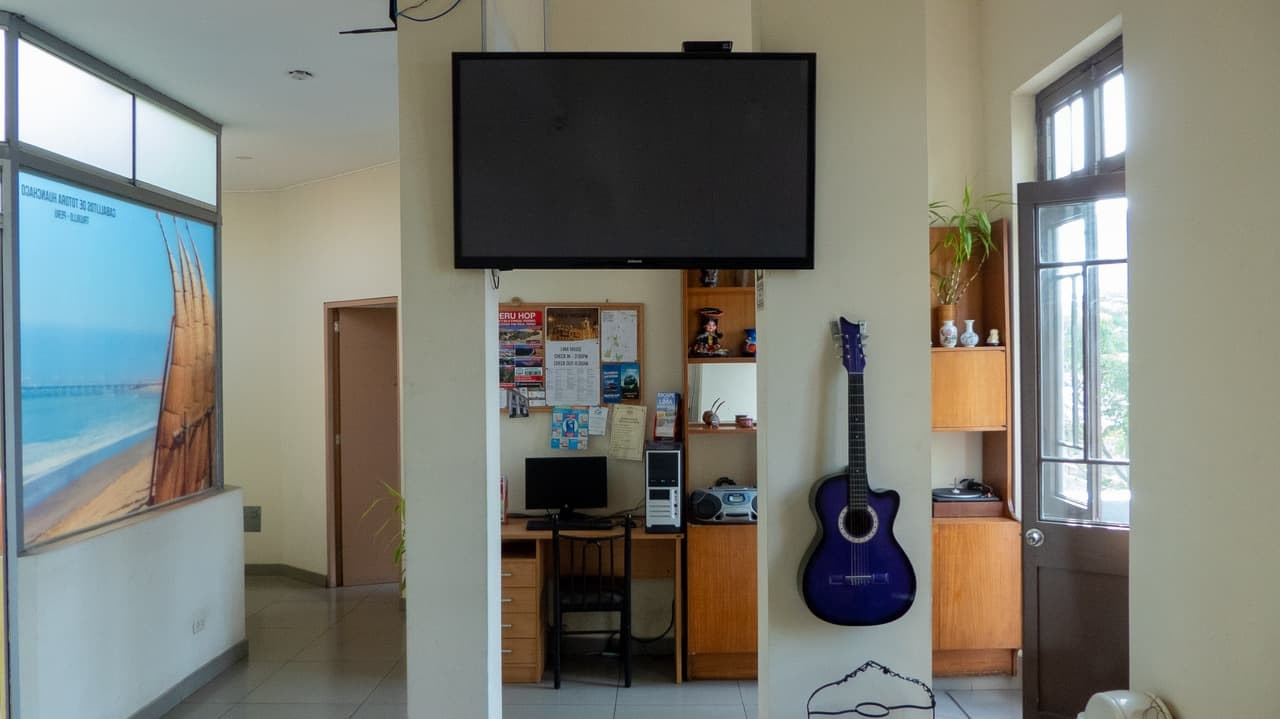 A Common Area With A Flatscreen TV and an Acoustic Guitar.