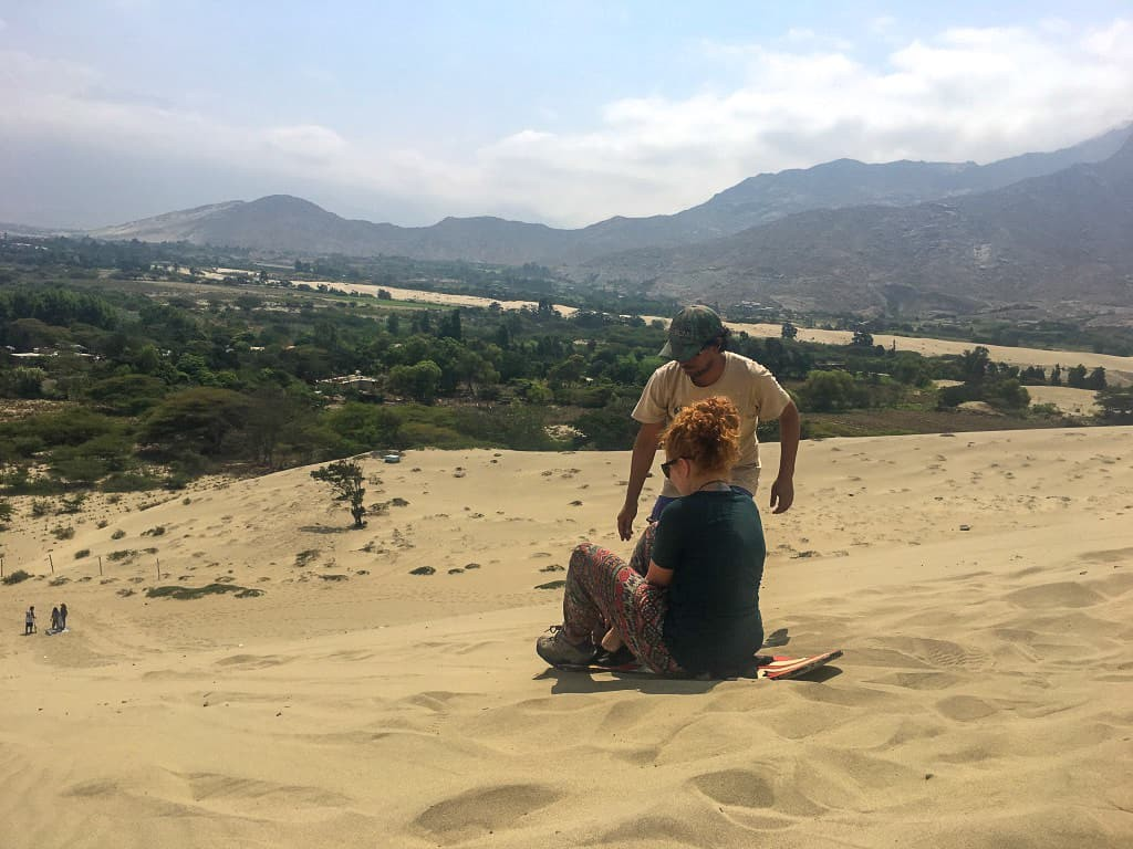 Victor is teaching the author on how to do the sitting position on the sandboard. Conache, Trujillo, Peru.