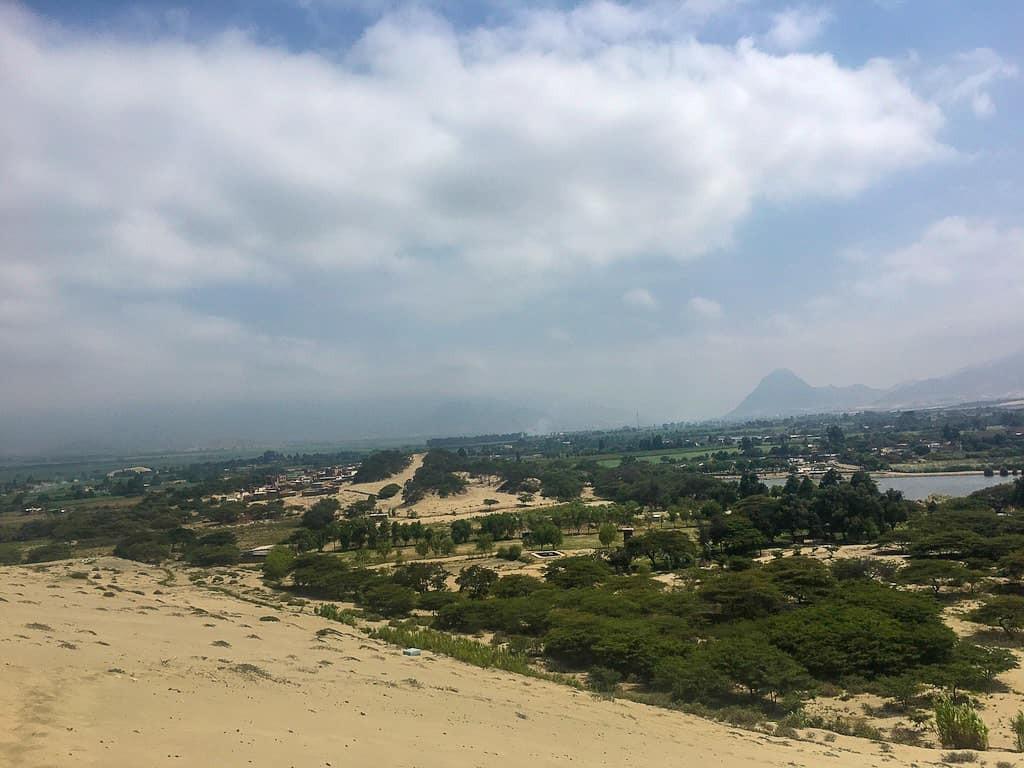Beautiful Conache Lake surrounded by huge and warm dunes for sandboarding in Trujillo, Peru.