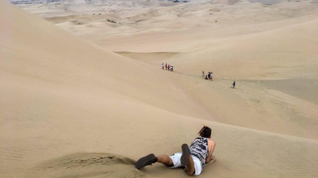 Person sandboarding in Huacachina, Peru- Full Day Ica Tour