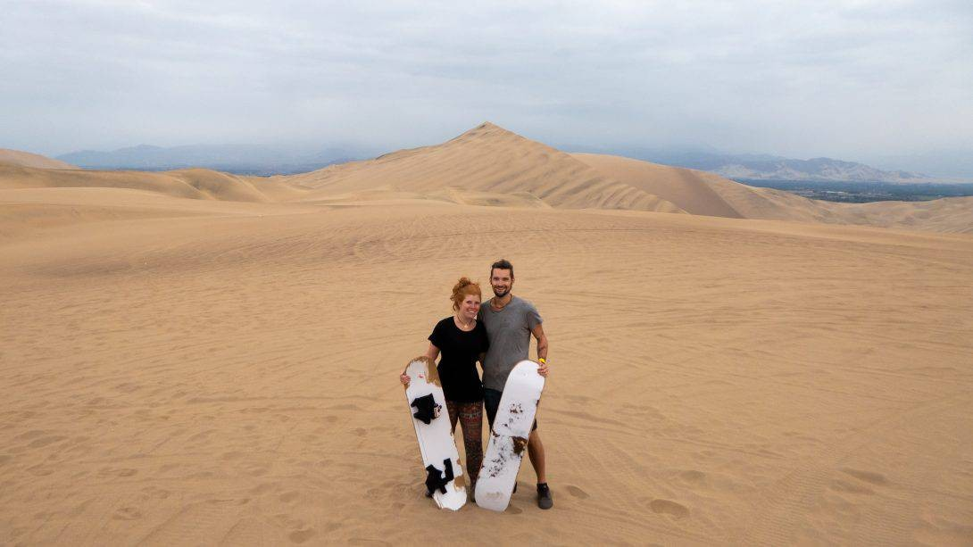 Two people with sandboards on Banana's Adventure Hostel trip