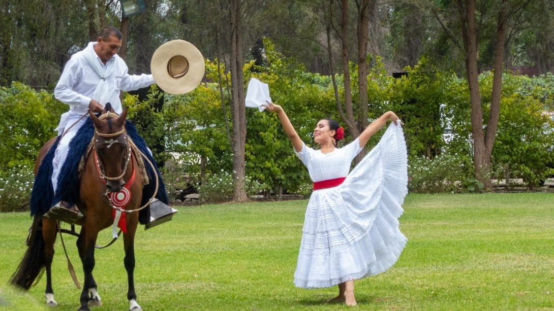 Peruvian Marinera dance with man on horse and woman.
