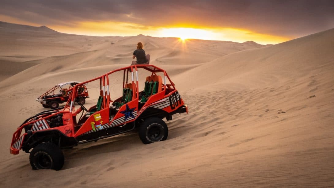 Girl watches sunset on dune buggy - Full Day Ica Tour