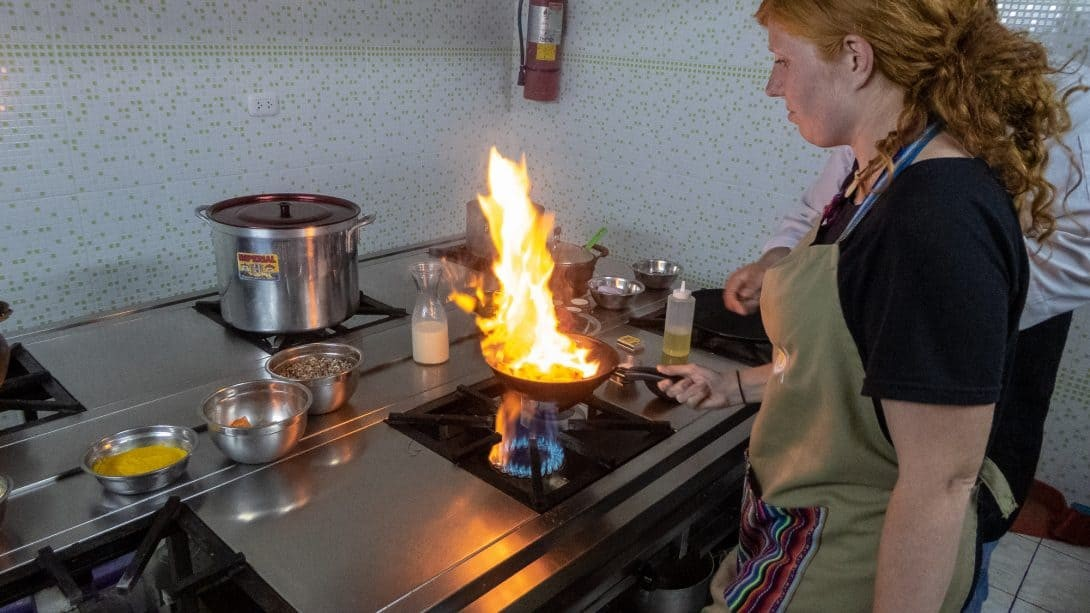 Cook with flaming pan at Cusco Culinary cooking school
