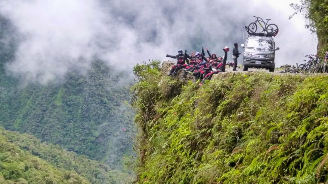 A Group Of Bikers Sit On The Edge Of Bolivia's Death Road.