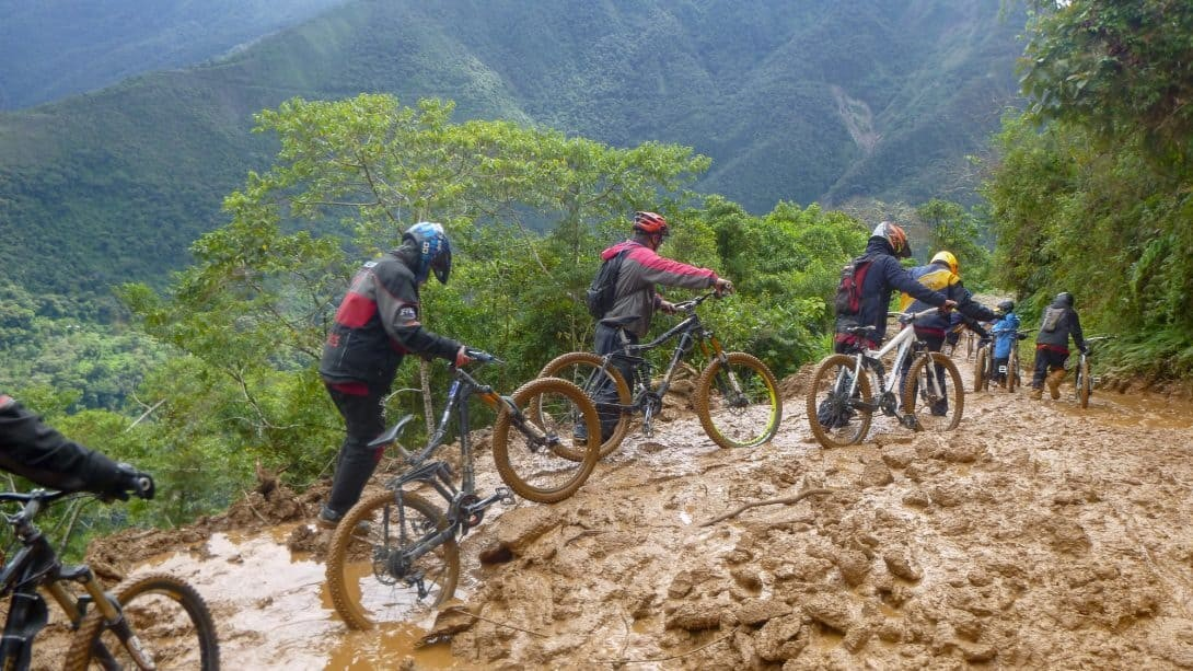 Cyclists Battle To Pull Their Bikes Through The Mud on North Yungas Road Bolivia