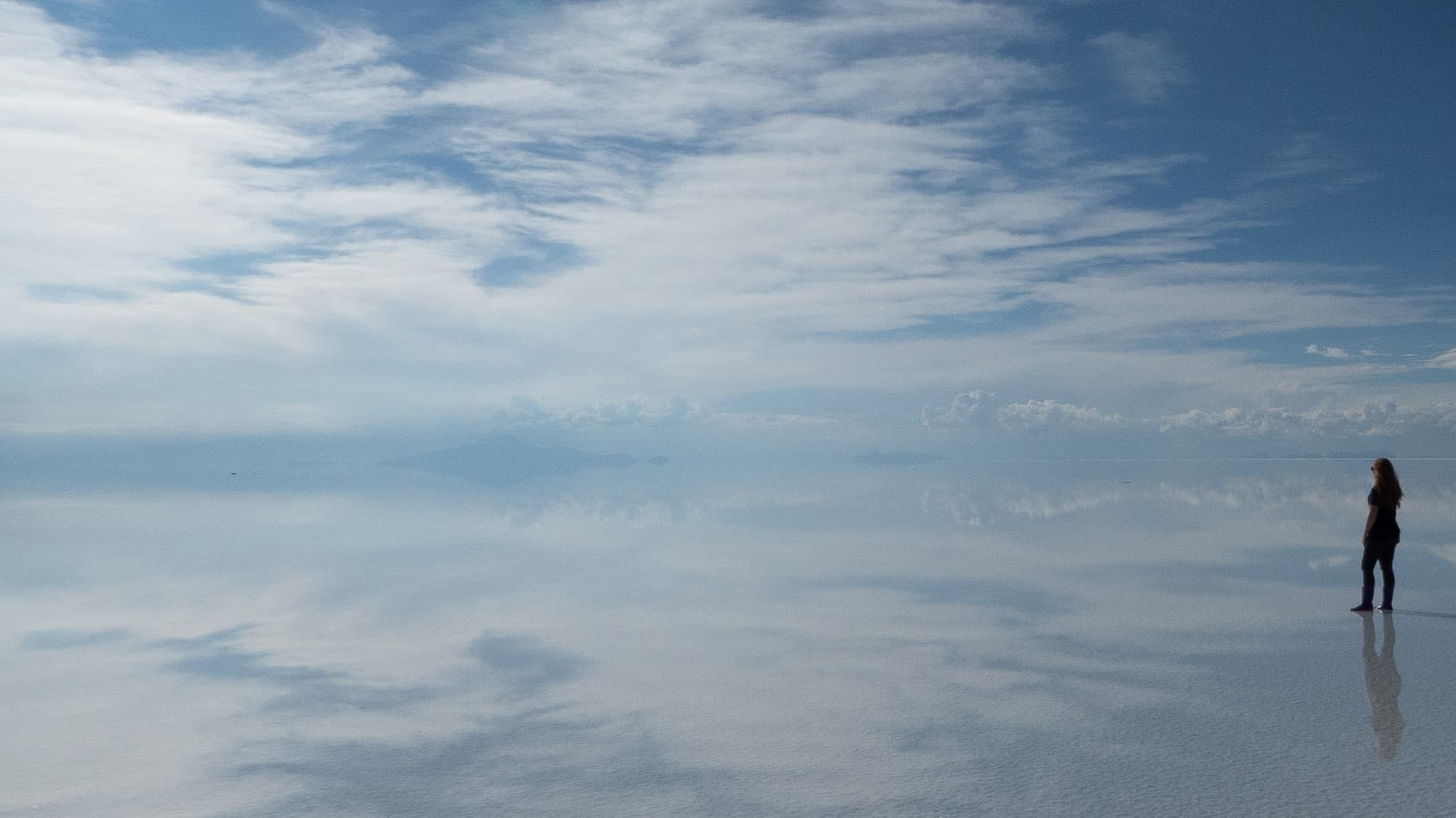 Sheree Stands At The Right Hand Side Of Reflected Blue Sky With Clouds on The Salar de Uyuni Salt Flats, Bolivia