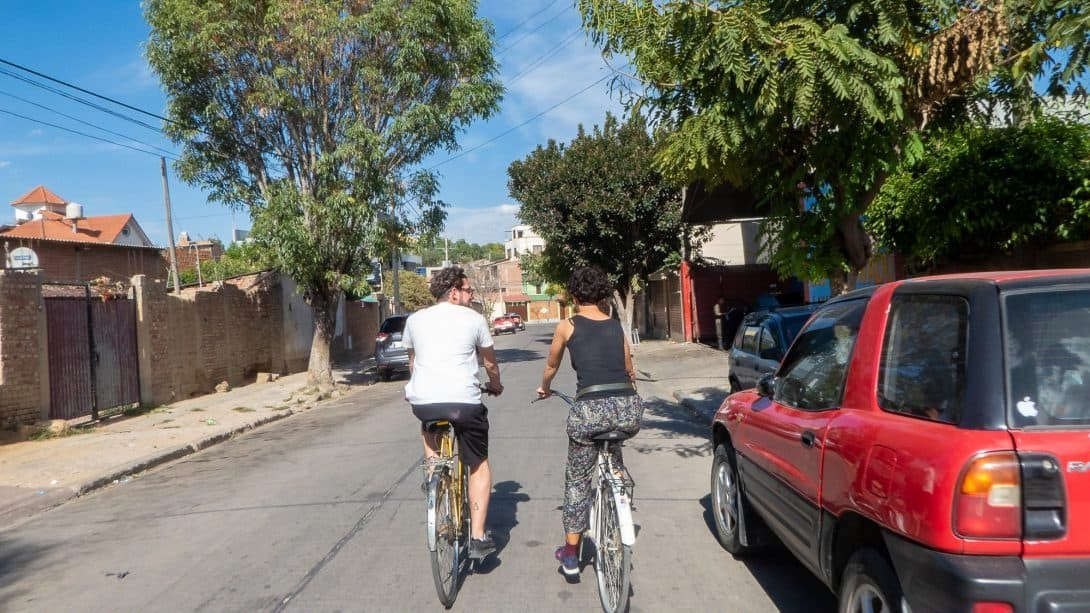 Two people cycling down a street in Cochabamba