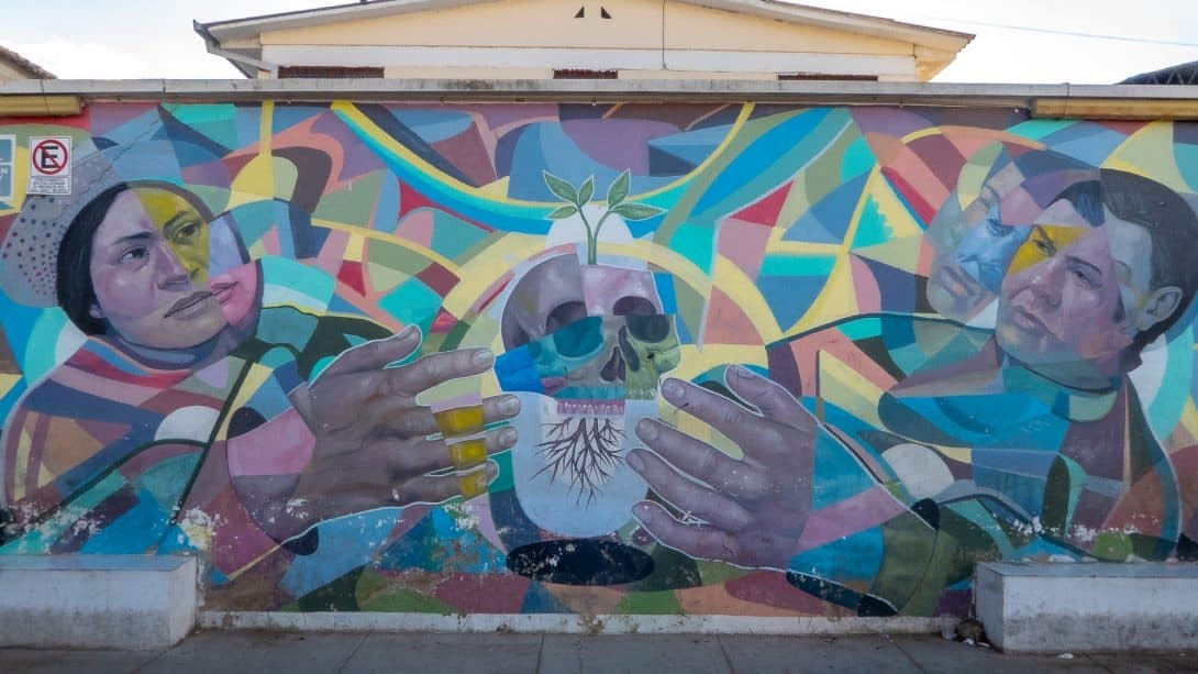Mural with people and skulls in Cochabamba