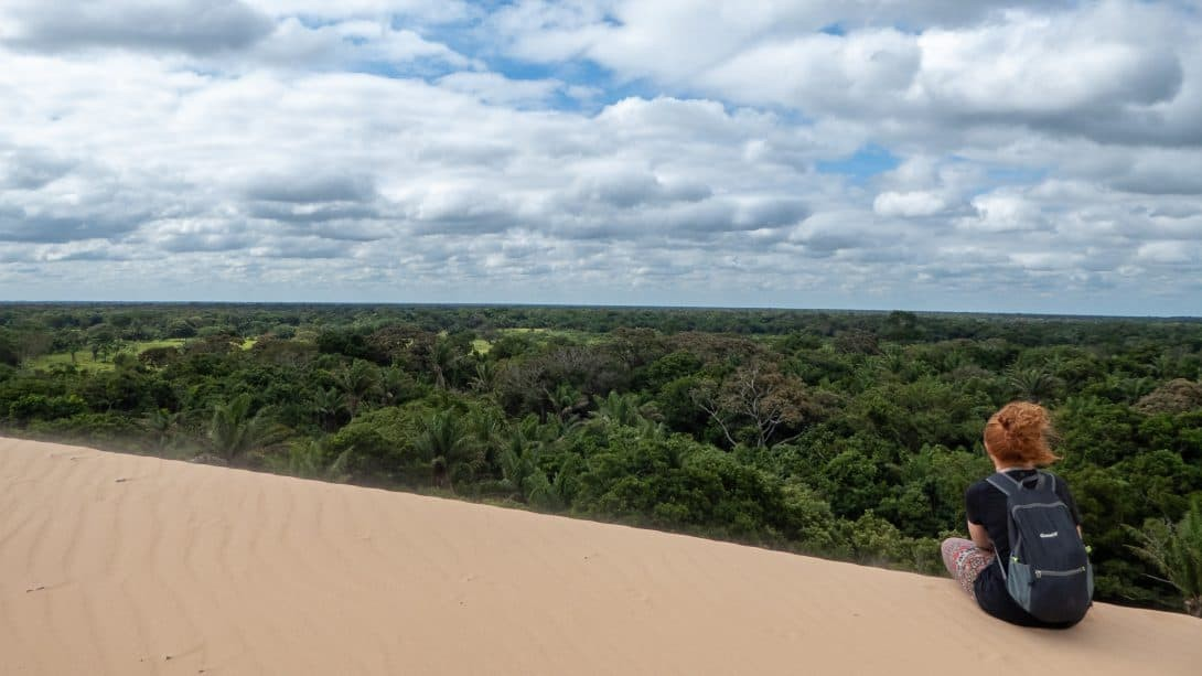 Girl sits on sand dune overlooking jungle