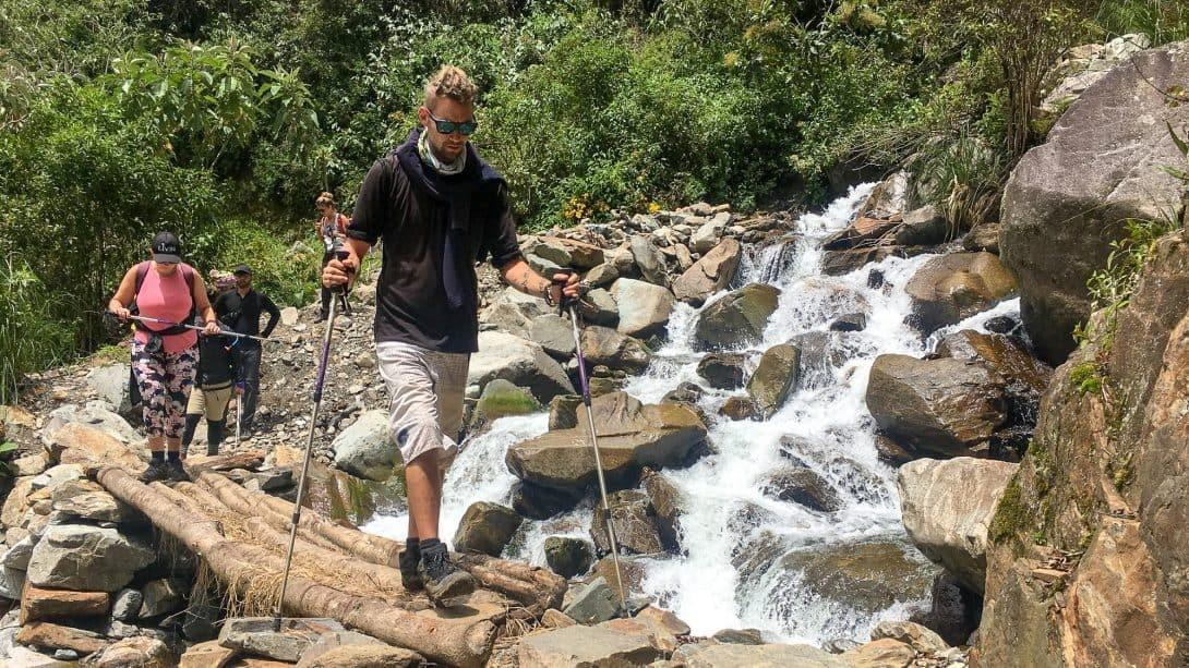 Man with hiking poles crosses bridge