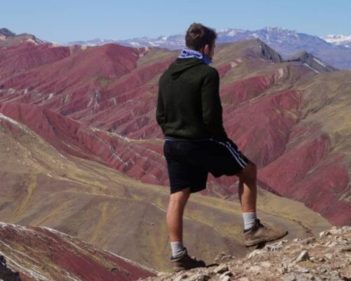 Man looks out over red mountains
