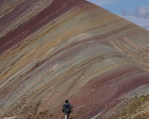 Man in front of alternative rainbow mountain