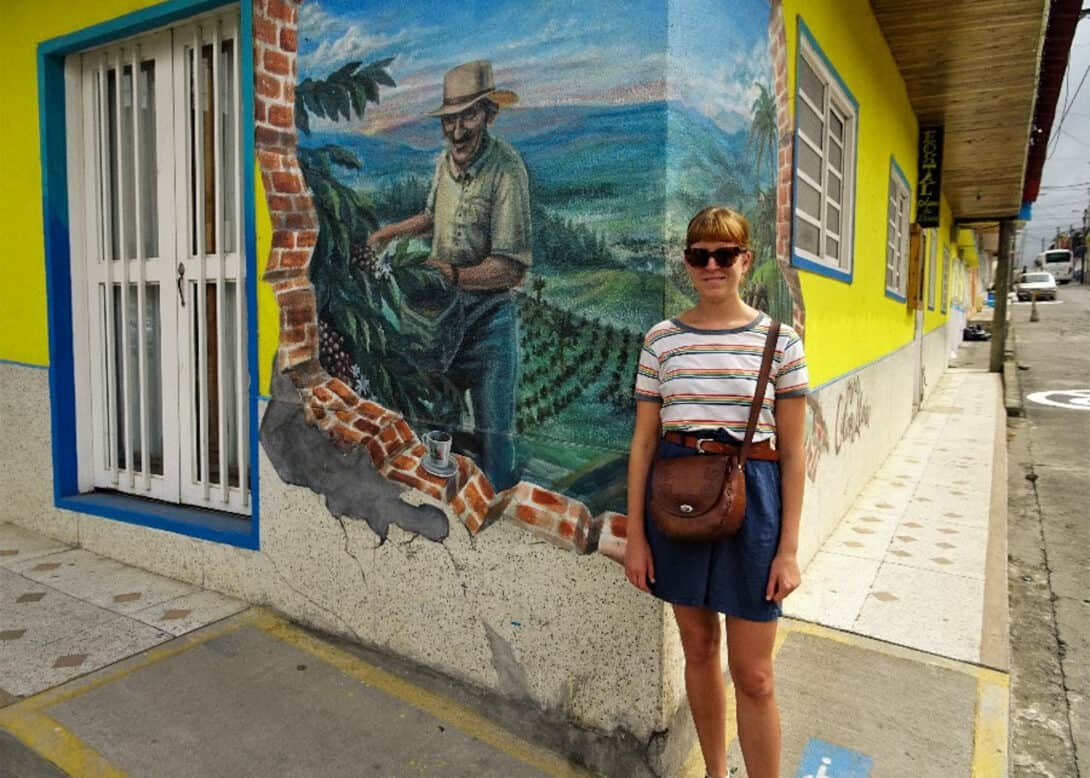 Girl in front of coffee mural in Colombia