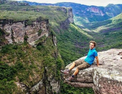 Man sits on high mountain rock overlooking valley.