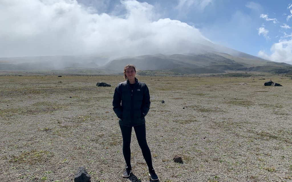 Girl stands in front of Cotopaxi Volcano.