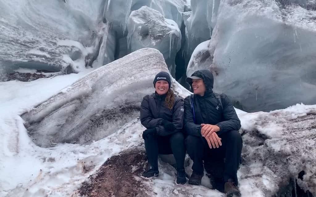 Couple sit on Cotopaxi Volcano glacier.