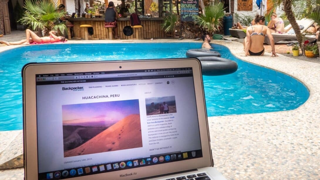 Macbook open in front of swimming pool