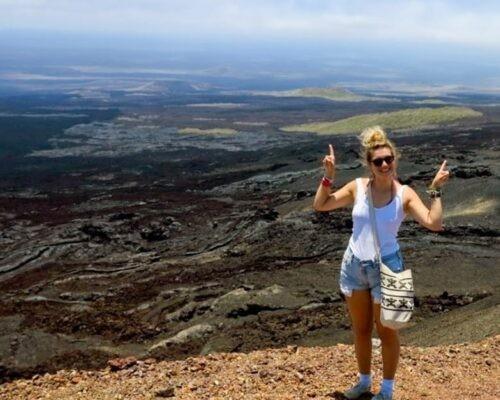Girl standing on lava flows at Sierra Negra Volcano