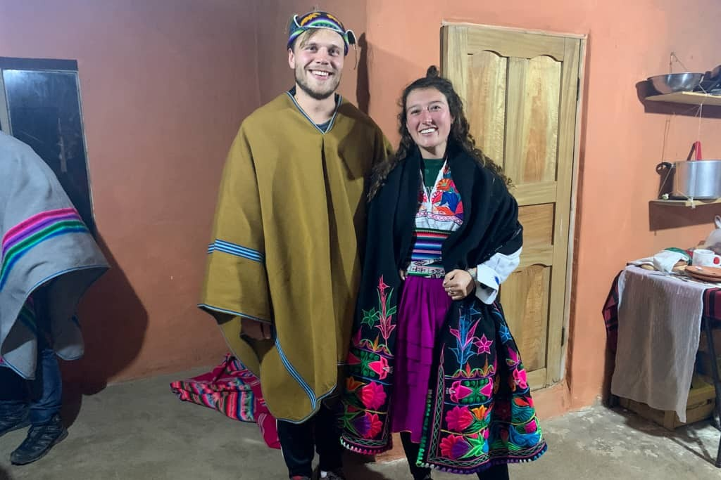Two tourists dressed up in traditional Peruvian clothing.