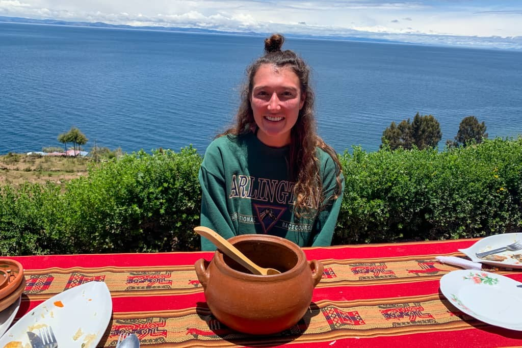 Girl smiling in front of soup pot.