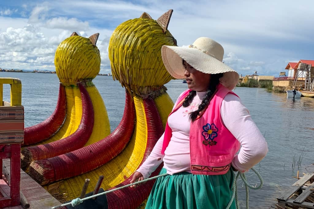 Young Peruvian woman next to reed boat.
