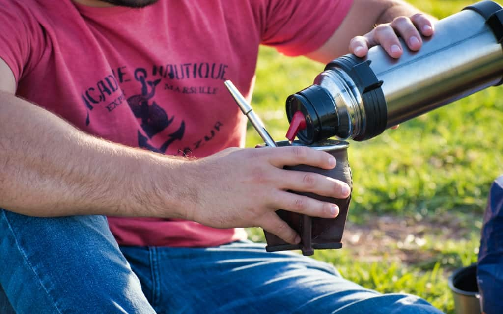 Man pouring mate in park
